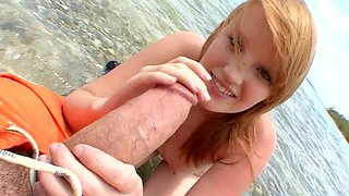A smiling blue eyed honey is playing with a dick on the beach