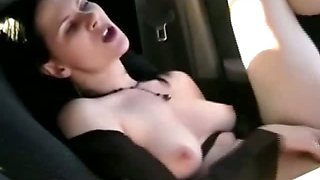 Brunette babe playing with her pussy inside the car