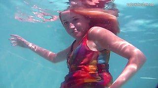 Saucy underwater teen flashes her assets