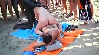 Interracial threesome on a nude beach with lots of spectators