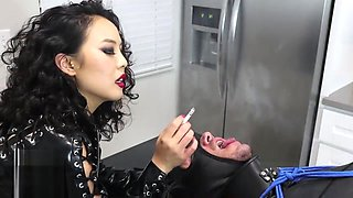 Rubber Mistress An Li uses her human ashtray