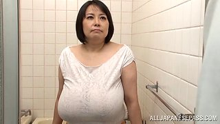 Huge-breasted mature Japanese lady gives a titjob to a horny man