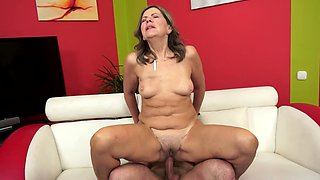 A granny that loves to fuck is in the bed with a younger man