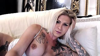 Tattooed blonde shemale with big tits drills her anal hole